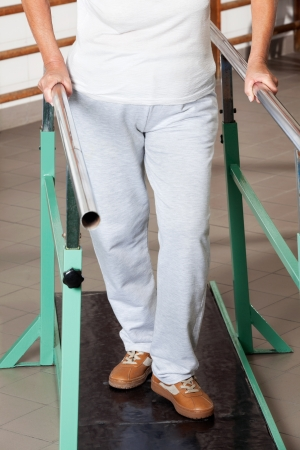 Low section of a senior woman walking with the help of support bars at hospital gym photo