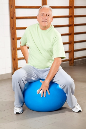 Full length of a senior man sitting on fitness ball at hospital gym photo