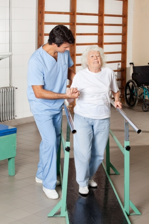 Full length portrait of a physical therapist assisting tired senior woman on walking track at hospital gym photo