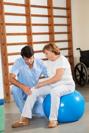 Young physical therapist examining senior woman s knee at hospital gym photo