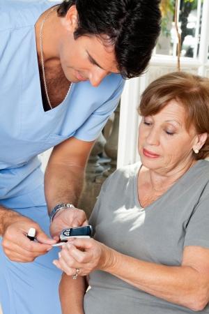 diabetes: Mujer enfermera de medici�n de glucosa en la sangre el nivel de prueba con gluc�metro y tiras de la muestra Foto de archivo