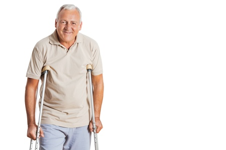 fisico: Retrato de la sonrisa hombre mayor con muletas de pie sobre fondo blanco