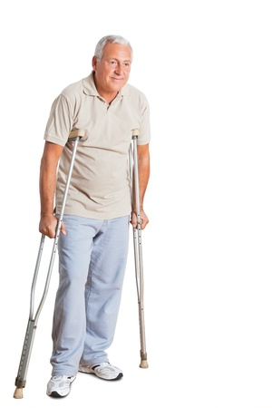 Full length of a senior man on crutches looking away over white background Stock Photo - 13800125