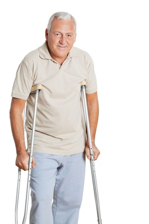 Portrait of happy senior man on crutches isolated over white background