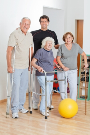 physical: Full length happy portrait of disabled senior people with trainer