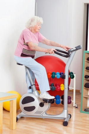 Full length of senior woman exercising on bike in gym photo