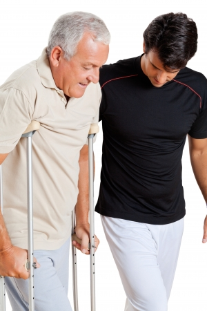 Trainer helping senior man with crutches to walk over white background photo