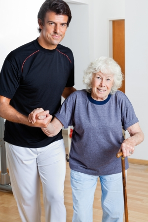 physical therapist: Portrait of a happy trainer assisting woman with walking stick Stock Photo