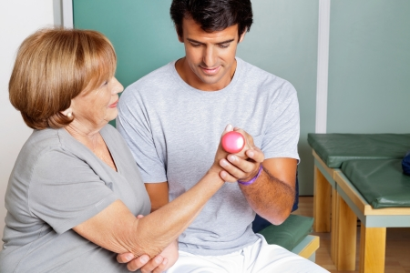 Young therapist giving muscle training for elbow joint at clinic Stock Photo - 13800163