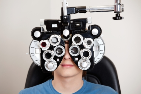 eye test: Boy sitting while undergoing an eye test with phoropter in the clinic