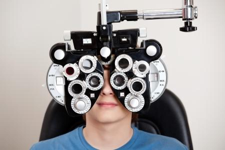 diopter: Ni�o sentado mientras se somete a un examen ocular con el for�ptero en la cl�nica