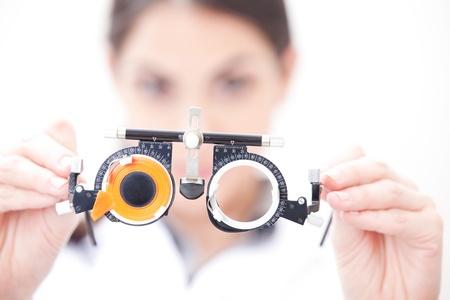 Optometrista la celebración de unas gafas de prueba de los ojos