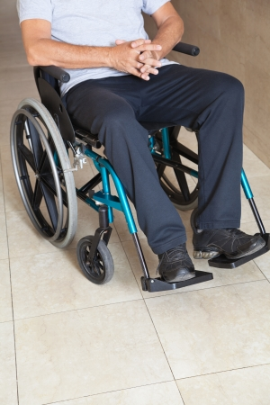Low section of a senior man sitting in a wheelchair at hospital corridor photo