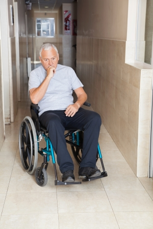 Full length of depressed senior man sitting in a wheelchair at hospital corridor photo