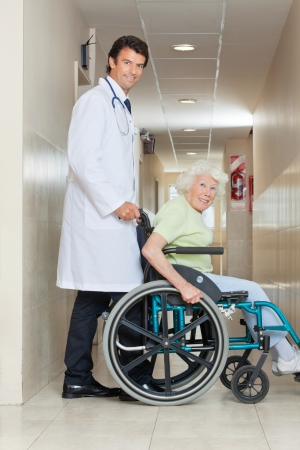 Side view of a happy young doctor assisting senior woman sitting in a wheel chair photo