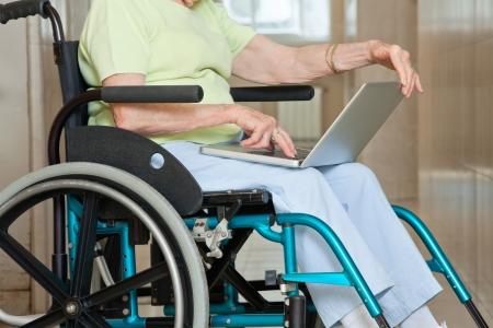 Secci�n del medio de la mujer mayor sentada en silla de ruedas, utilizando equipo port�til en el hospital Foto de archivo - 13871980