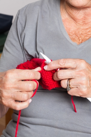 Mid section of senior woman knitting photo