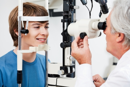 medical exam: Smiling boy getting visual field test done by the optometrist