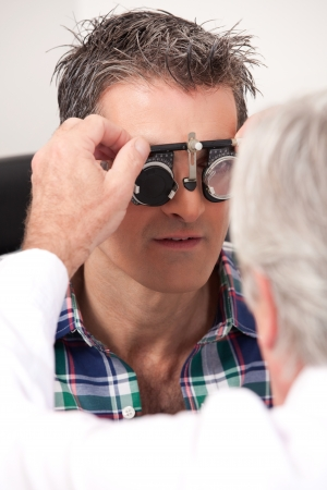 near sighted: Optometrist using measuring spectacles on patient Stock Photo