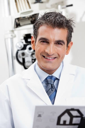 Portrait of a friendly eye doctor smiling at his clinic photo
