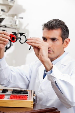 Optometrist checking the lens of trial frames with concentration for eye examination photo