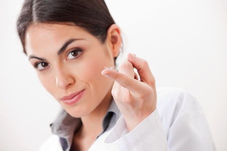 progressive: Young female optometrist showing contact lens