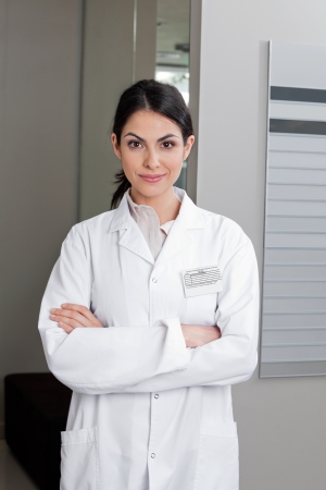 lab coat: Portrait of a confident female optometrist smiling with arms crossed Stock Photo