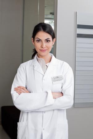 lab coat: Retrato de un optometrista de confianza en las mujeres sonriendo con los brazos cruzados Foto de archivo