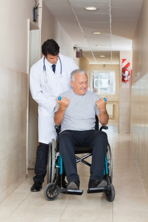 Doctor giving muscle training to the senior man sitting in a wheelchair photo