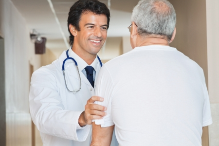 patient and doctor: Happy young doctor assisting senior man in the hospital Stock Photo