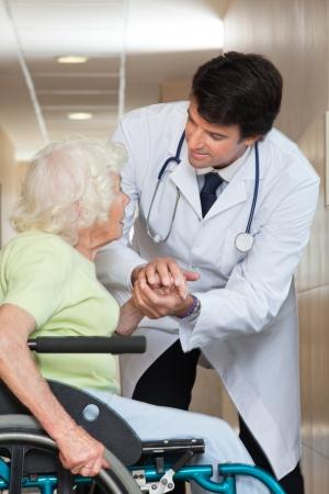 male doctor: Felice giovane medico maschio confortante paziente anziano in ospedale