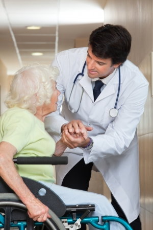 Happy young male doctor comforting senior patient at hospital photo