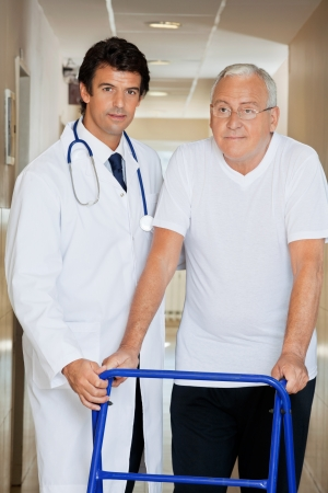 Young handsome doctor helping an old man with his walker Stock Photo - 14031663