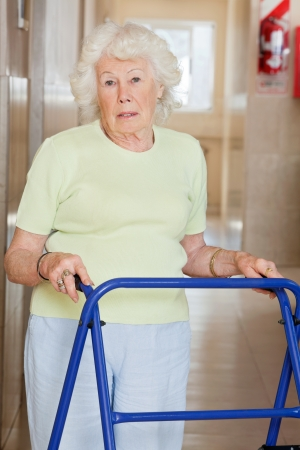 Portrait of a senior woman in hospital using Zimmer frame photo