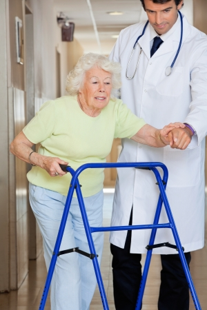Young male doctor showing way to the patient using walker photo