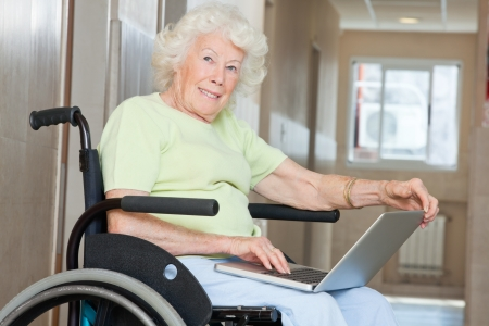 Happy senior woman sitting in wheelchair using laptop at hospital photo