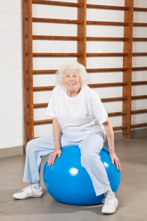 Full length portrait of a happy senior woman sitting on fitness ball at hospital gym photo