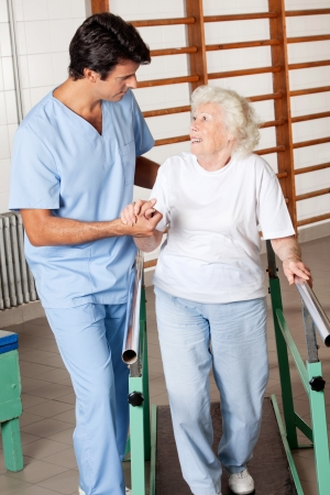 Happy senior woman on walking track looking at physical therapist photo