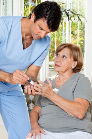 Male nurse checking sugar level of patient through glucometer Stock Photo - 14031743