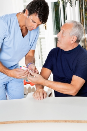 Male nurse checking sugar level of senior man through glucometer photo