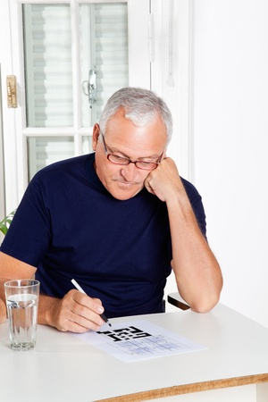 crossword puzzle: Senior man playing leisure games with glass of water in foreground Stock Photo