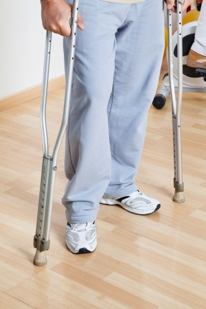 Low section of a woman standing with crutches on a wooden floor Stock Photo - 14031732