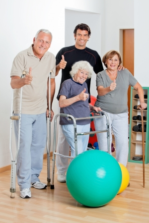 physical injury: Portrait of disabled senior people with trainer showing thumbs up sign
