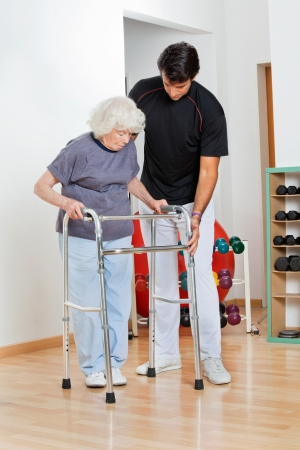 Full length of a trainer assisting senior woman in moving walker photo