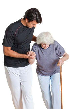 walking stick: Young trainer assisting senior woman holding walking stick over white background Stock Photo