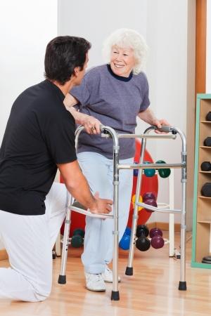 marcheur: Happy senior woman avec marchette regardant formateur