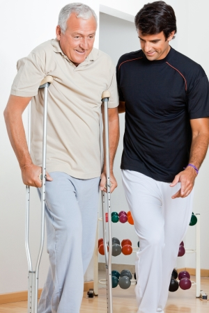 physical therapy: Trainer helping senior man with crutches to walk