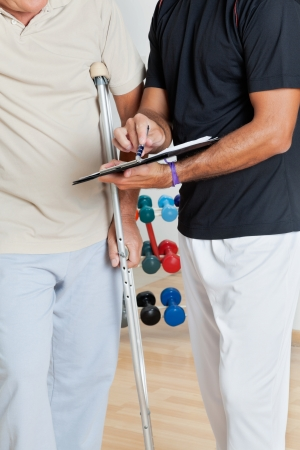 Mid section of trainer holding clipboard while standing with senior man on crutches Stock Photo - 14031736