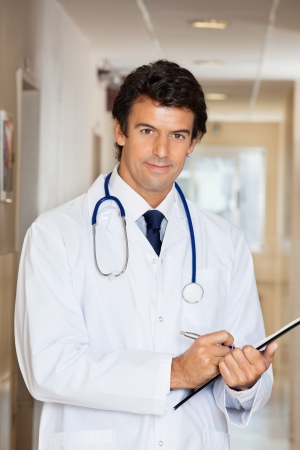 doctor writing: Portrait of young doctor writing report on clipboard Stock Photo