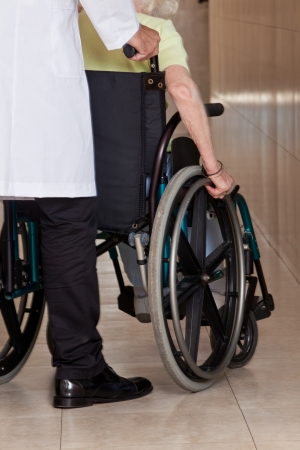 assisting: Doctor with patient on wheel chair at hospital  Stock Photo